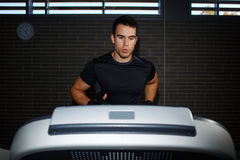 handsome brunette man at workout in gym running fast on a treadmill Stock Photography