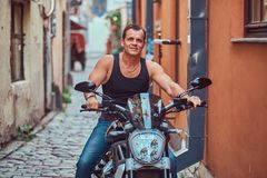 A handsome brutal biker, ride on a motorcycle, in a narrow old Europe street. A handsome brutal biker dressed in a black t-shirt and jeans, with a charming Royalty Free Stock Photo