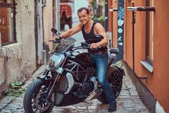 A handsome brutal biker, ride on a motorcycle, in a narrow old Europe street. A handsome brutal biker dressed in a black t-shirt and jeans, with a charming Royalty Free Stock Image