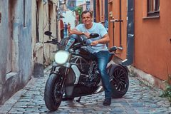 A handsome brutal biker, ride on a motorcycle, in a narrow old Europe street. A handsome brutal biker dressed in a white t-shirt and jeans, with a charming Stock Image