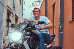 A handsome brutal biker, ride on a motorcycle, in a narrow old Europe street. A handsome brutal biker dressed in a white t-shirt and jeans, with a charming Stock Photos