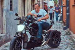 A handsome brutal biker, ride on a motorcycle, in a narrow old Europe street. A handsome brutal biker dressed in a white t-shirt and jeans, with a charming Royalty Free Stock Photo