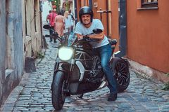 A handsome brutal biker, ride on a motorcycle, in a narrow old Europe street. A handsome brutal biker dressed in a white t-shirt and jeans, with a charming Royalty Free Stock Images