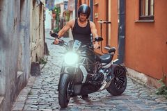 A handsome brutal biker, standing near a motorcycle, in a narrow old Europe street. A handsome brutal biker dressed in a black t-shirt and jeans, standing near Stock Image