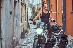 A handsome brutal biker, standing near a motorcycle, in a narrow old Europe street. A handsome brutal biker dressed in a black t-shirt and jeans, with a Royalty Free Stock Photo