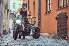 A handsome brutal biker, standing near a motorcycle, in a narrow old Europe street. A handsome brutal biker dressed in a black t-shirt and jeans, with a Stock Photos