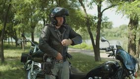 Serious biker dressing up black leather jacket stock footage