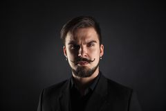 Handsome brutal guy with beard on dark background Royalty Free Stock Image