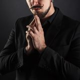 Handsome brutal guy with beard on dark background. In studio Royalty Free Stock Photos