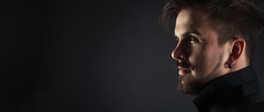 Handsome brutal guy with beard on dark background. In studio Stock Photo