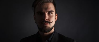 Handsome brutal guy with beard on dark background. In studio Royalty Free Stock Image