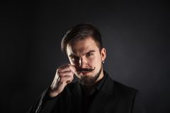 Handsome brutal guy with beard on dark background. In studio Stock Image