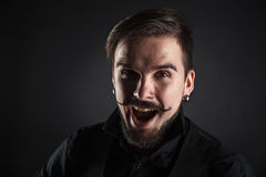 Handsome brutal guy with beard on dark background Stock Photos