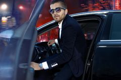 Handsome brutal man in luxury car. Night life stock photography