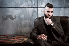 A handsome brutal young stylish brunette man with a beard sits in a leather chair on a gray background, drinks whiskey. The hairdresser man in glasses cuts and stock photos