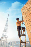 Handsome builder climb on ladder up. Royalty Free Stock Photos