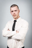 Handsome buisnessman with crossed hands. Looking angry over gray background Stock Images