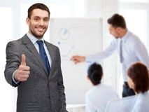 Handsome buisnessman showing thumbs up in office. Business, gesture and office concept - handsome buisnessman showing thumbs up in office stock photography