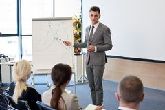 Handsome Business Coach. Full length portrait of handsome business coach giving presentation during training seminar in conference hall, copy space Stock Photo