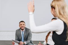 Handsome business coach looking at participant with raised hand during training. In hub royalty free stock photography