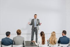 Handsome business coach standing on stage and gesturing during training. In hub stock photo