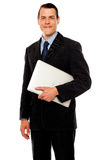 Handsome business executive holding laptop stock images