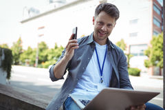 Handsome business executive holding mobile phone and laptop Stock Photography