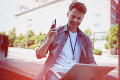 Handsome business executive holding mobile phone and laptop Stock Photo