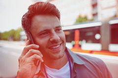 Handsome business executive talking on mobile phone at street Royalty Free Stock Images