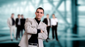 Handsome business man. With colleagues at the back Royalty Free Stock Photo