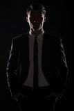 Handsome business man in black suite, backlight.  royalty free stock photography