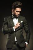 Handsome business man fixing his tuxedo Stock Photos
