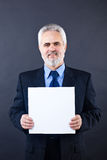 Handsome business man holding blank card. Studio shot of a smiling handsome business man holding blank card Stock Image