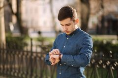 Handsome business man look at the watch in the city. Man ajust the exact time on the watch.  royalty free stock photo