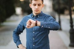 Handsome business man look at the watch in the city. Man ajust the exact time on the watch.  stock photo