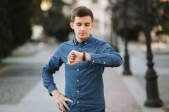 Handsome business man look at the watch in the city. Man ajust the exact time on the watch.  royalty free stock image
