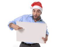 Handsome business man in santa christmas hat pointing blank billboard Stock Image