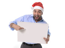 Handsome business man in santa christmas hat pointing blank billboard Stock Photo