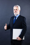 Handsome business man showing thumbs up sign. Studio shot of a smiling handsome business man showing thumbs up sign Royalty Free Stock Images