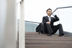 Handsome business man speaking mobile phone sitting in the stair Stock Image