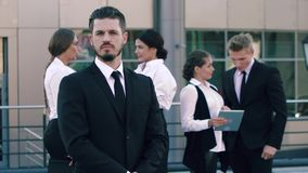 Handsome business man standing in the foreground, in the background his fellow workers are standing. And discussing the results of a meeting stock footage