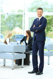 Handsome business man standing with his collegues in background Stock Photo