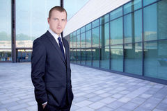 Handsome business man standing on street against office building Royalty Free Stock Photography