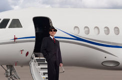 Handsome business man on the steps of a private jet. Wearing a suit and hat Royalty Free Stock Photos