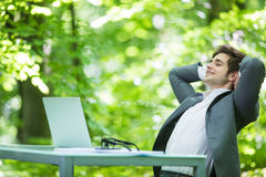 Portrait of young handsome business man in suit relax at laptop at office table hands over head in green forest park. Business con. Handsome business man in suit royalty free stock images