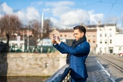 Handsome business man taking a picture with mobile phone outdoors royalty free stock image