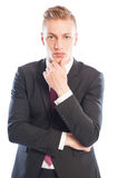 Handsome business man thinking while touching his chin Stock Photography