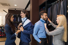 Handsome Business Man Trying Clothes Woman Fashion Shop, Customers Choosing In Retail Store. Handsome Business Man Trying Suit Clothes Woman Assistant Help Royalty Free Stock Photo
