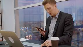 Handsome business man using mobile phone at table on evening window background stock footage