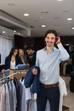 Handsome Business Man Wear Formal Suit Holding Jacket In Hands In Modern Menswear Shop. Over Latin Male Paying For Clothes Royalty Free Stock Photos